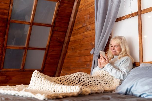 Donna senior di vista frontale a letto con il cellulare Foto Gratuite