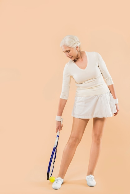 Donna senior moderna che gioca a tennis Foto Gratuite
