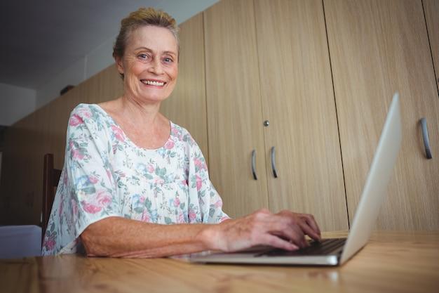 Donna senior sorridente che per mezzo di un computer portatile Foto Premium