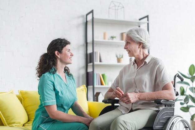 Donna senior sorridente che si siede sulla sedia a rotelle che esamina infermiera femminile Foto Gratuite