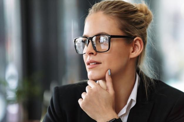 Donna seria di affari che si siede in caffè che osserva da parte. Foto Gratuite