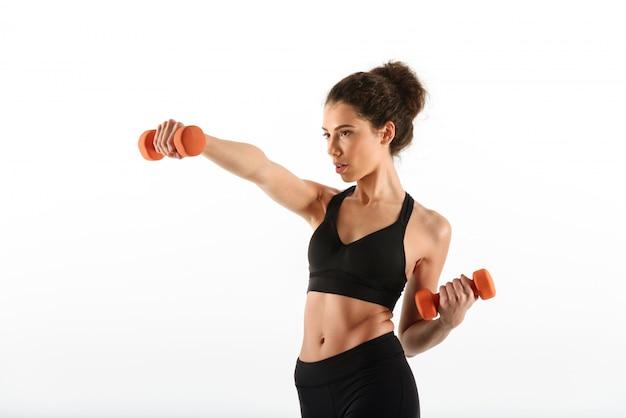 Donna seria di forma fisica che fa esercizio con le teste di legno e distogliere lo sguardo Foto Gratuite