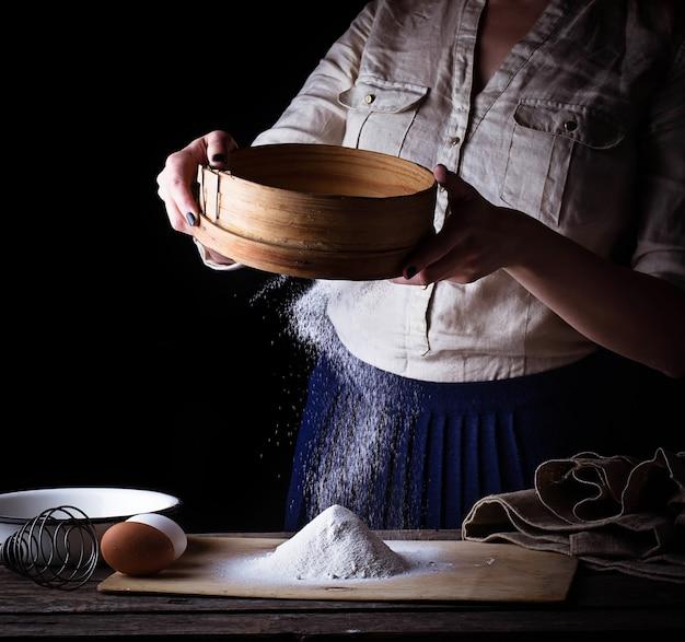 Donna setacciare la farina al setaccio Foto Premium