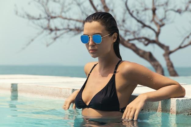 Donna sexy che si distende in piscina Foto Premium