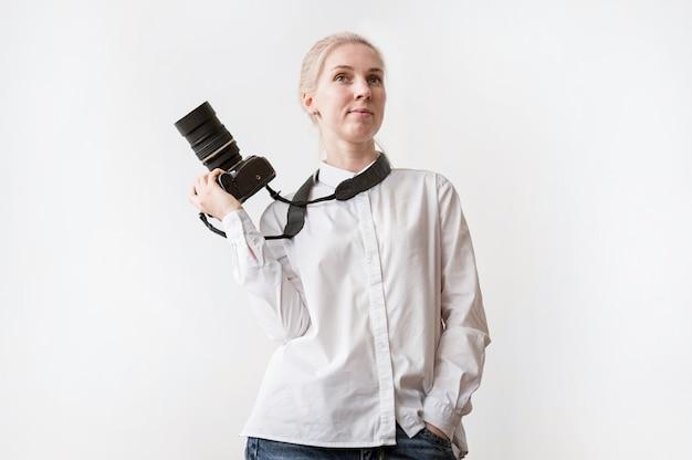 Donna sicura che tiene una foto della macchina fotografica Foto Gratuite