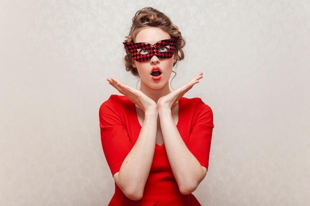 Donna sorpresa che indossa una maschera di carnevale Foto Gratuite