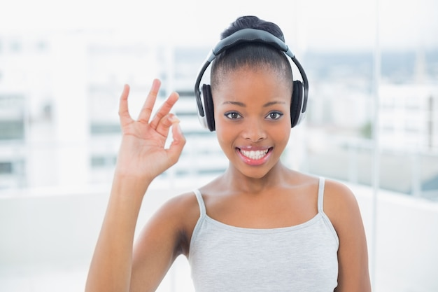 Donna sorridente che ascolta la musica con le cuffie e segno giusto shwoing Foto Premium