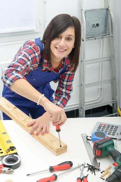Donna sorridente che monta le plance di legno facendo uso del cacciavite Foto Premium