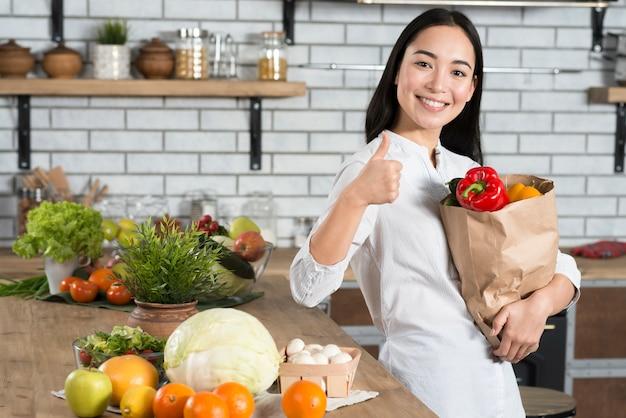 Donna sorridente che mostra pollice sul segno mentre tiene la borsa marrone della drogheria Foto Gratuite