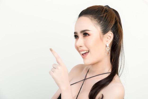 Donna sorridente che punta il dito sul lato. ritratto isolato su bianco Foto Gratuite