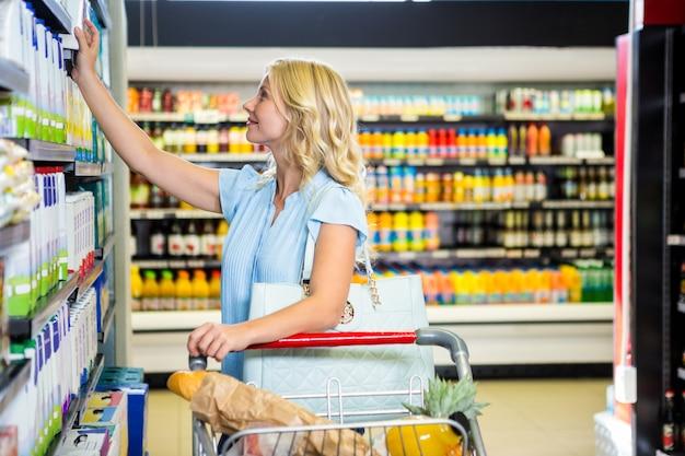 Donna sorridente che seleziona i prodotti lattiero-caseari Foto Premium