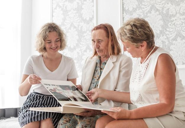 Donna sorridente che si siede con sua madre e nonna che guardano album di foto a casa Foto Gratuite