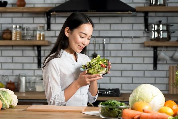Donna sorridente che tiene bicchiere di ciotola con insalata Foto Gratuite