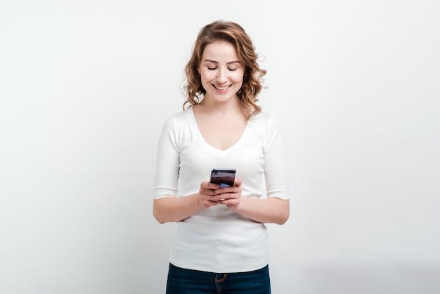 Donna sorridente che tiene un telefono in sua mano. Foto Premium