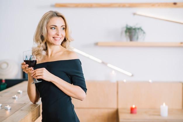 Donna sorridente che tiene vino di vetro Foto Gratuite