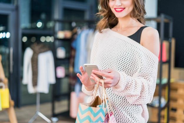 Donna sorridente che utilizza smartphone che sta nella sala d'esposizione Foto Gratuite
