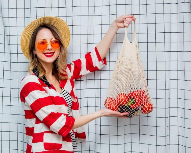 Donna sorridente con cappello e giacca a righe con sacchetto di rete Foto Premium