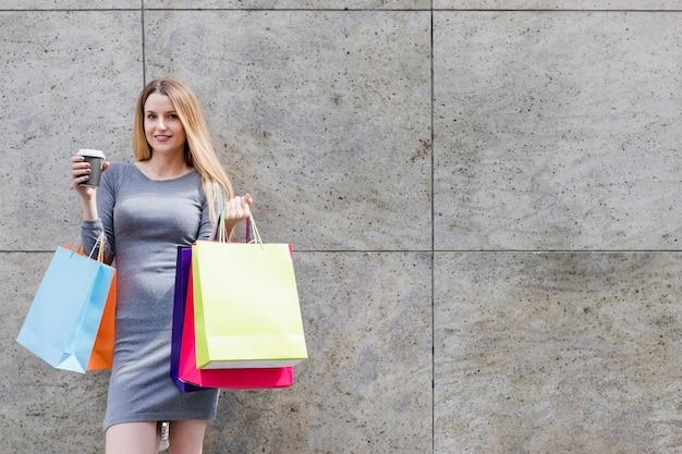 Donna sorridente con i sacchetti della spesa variopinti davanti alla parete Foto Gratuite