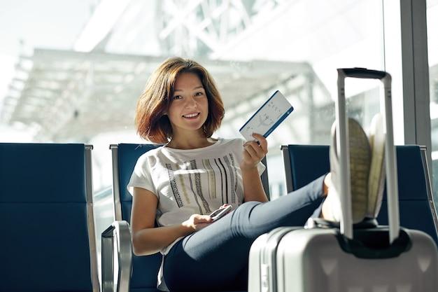 Donna sorridente con il biglietto e bagaglio in aeroporto. concetto di viaggio æreo con la giovane ragazza casuale che si siede con la valigia del bagaglio a mano al portone che aspetta in terminale. Foto Premium