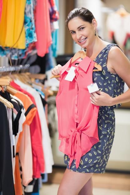 Donna sorridente e alzando la camicia Foto Premium