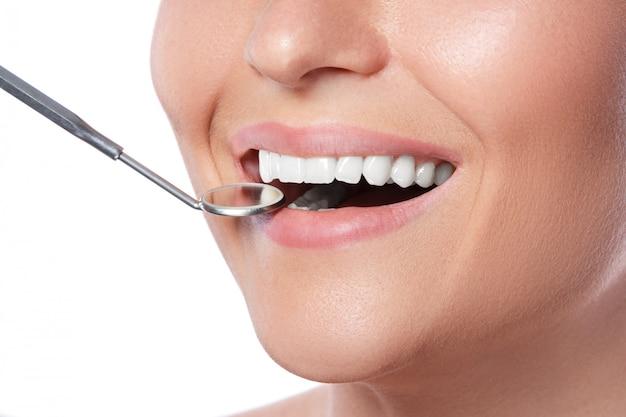 Donna sorridente e specchio dentale Foto Premium