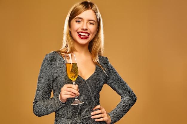 Donna sorridente felice in elegante abito glamour con un bicchiere di champagne. Foto Gratuite