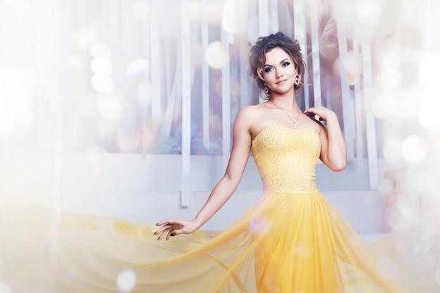 Donna sorridente in abito da sera giallo e con bella acconciatura, festa Foto Premium