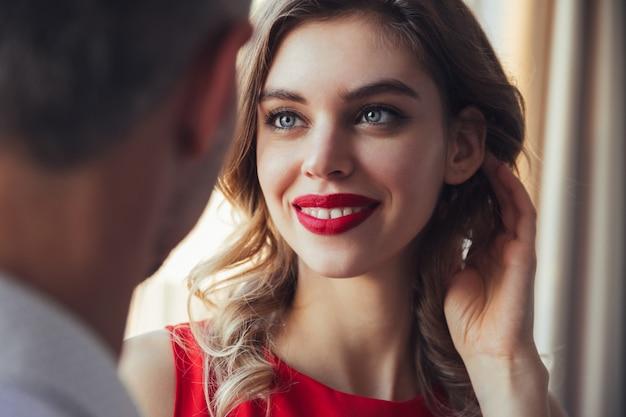 Donna sorridente in abito rosso e con le labbra rosse, guardando il suo uomo Foto Gratuite