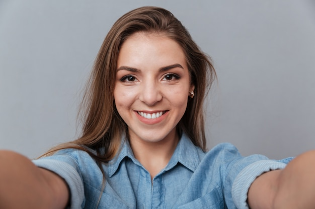 Donna sorridente in camicia che fa selfie in studio Foto Gratuite