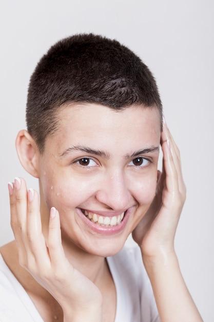 Donna sorridente naturale che guarda l'obbiettivo Foto Gratuite