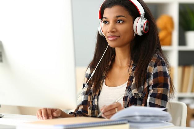 Donna sorridente nera che si siede nel luogo di lavoro indossando le cuffie Foto Premium