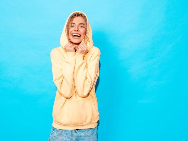 Donna spensierata che posa vicino alla parete blu in studio. divertimento del modello positivo Foto Gratuite