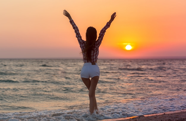 Donna spensierata felice sulla spiaggia che gode dell'estate Foto Premium