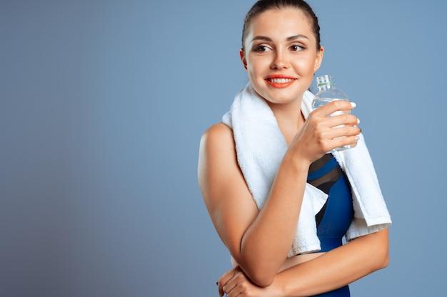 Donna sportiva adatta che tiene la bottiglia di acqua minerale in sua mano Foto Premium