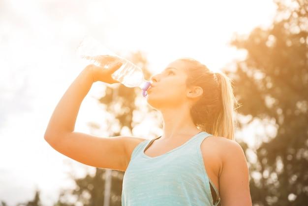 Donna sportiva che beve sulla pista dello stadio Foto Gratuite