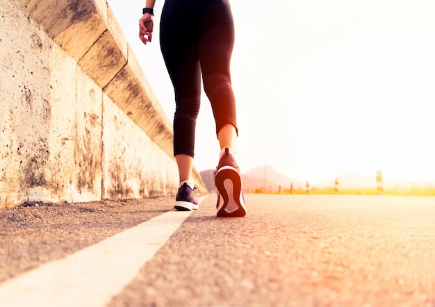 Donna sportiva che cammina verso il lato della strada. concetto di passaggio Foto Premium