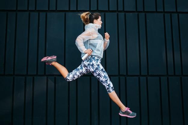 Donna sportiva che funziona nell'ambiente urbano Foto Gratuite