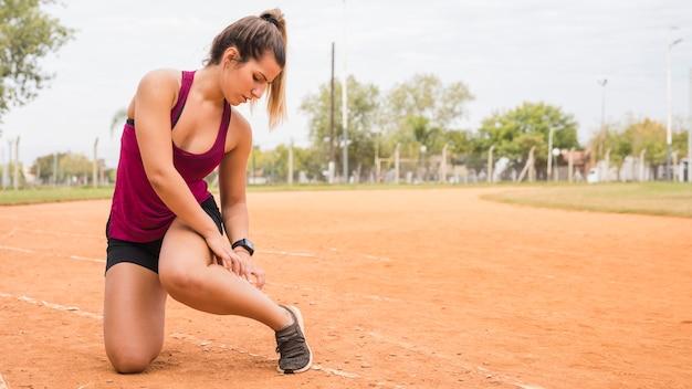 Donna sportiva che si estende sulla pista dello stadio Foto Gratuite