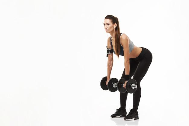 Donna sportiva di giovane forma fisica in cuffie che prepara le teste di legno della tenuta su bianco. Foto Gratuite