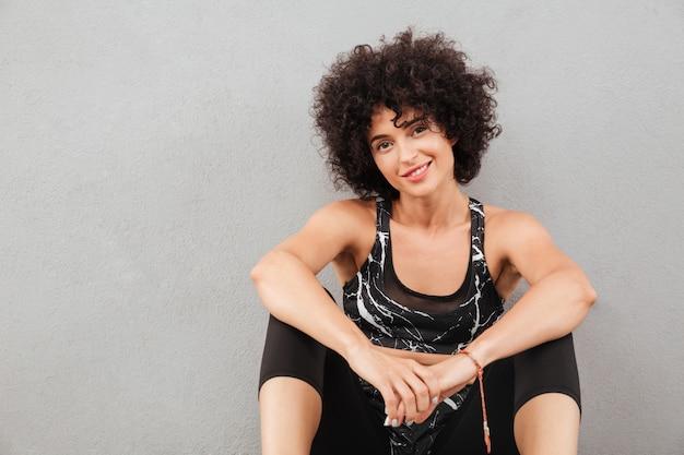 Donna sportiva piacevole che si siede sul pavimento Foto Gratuite