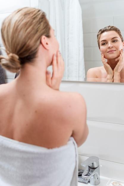 Donna spugna guardando nello specchio Foto Gratuite