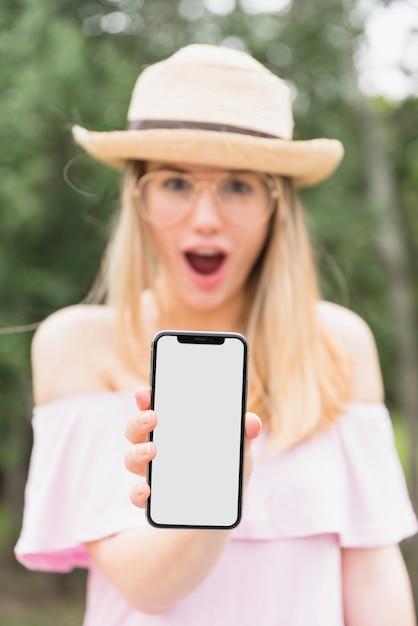 Donna stupita che tiene smartphone con schermo vuoto Foto Gratuite