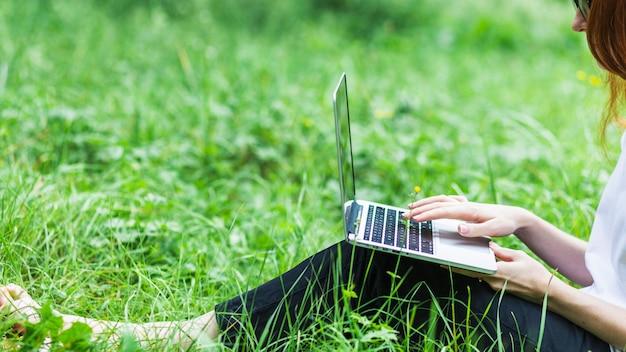 Donna su erba con il portatile Foto Gratuite