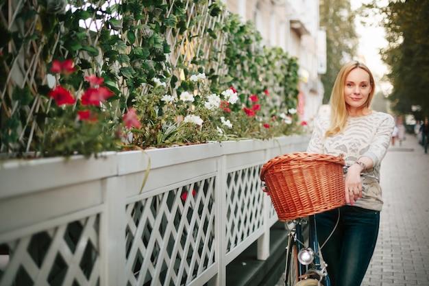 Donna su una bicicletta d'epoca in strada Foto Premium