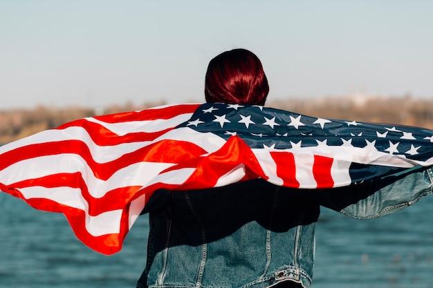Donna tornò in piedi e tenendo la bandiera americana Foto Gratuite
