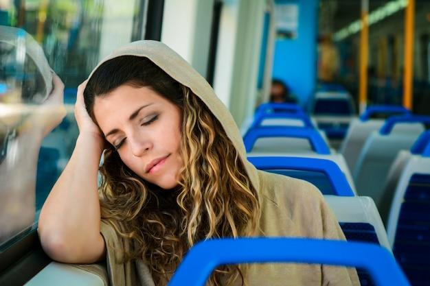 Donna urbana che dorme in un viaggio in treno accanto alla finestra. Foto Premium