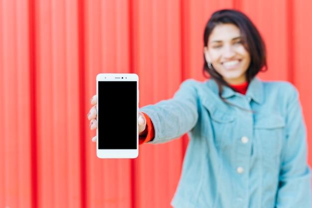 Donna vaga felice che mostra telefono cellulare contro fondo metallico rosso Foto Gratuite