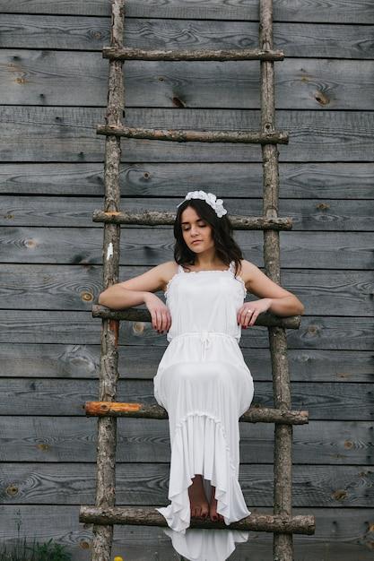 Donna vestita da sposa salendo le scale di legno Foto Gratuite