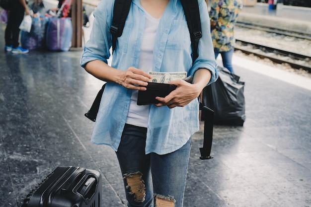 Donna viaggio con zaino dollari americani in portafoglio, piano finanziario per il turismo. Foto Premium