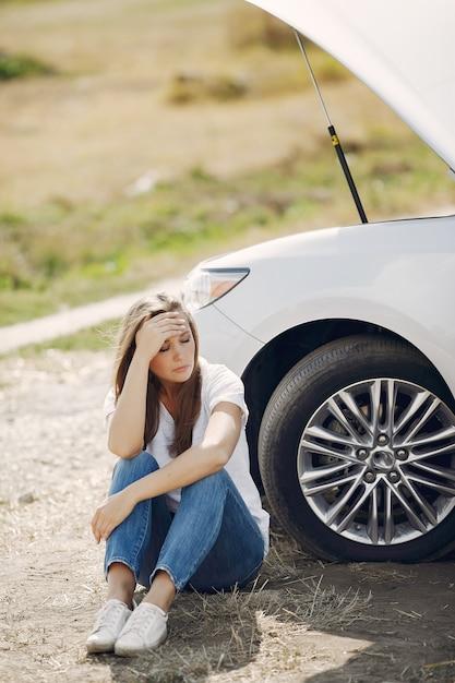 Donna vicino alla macchina rotta per chiedere aiuto Foto Gratuite